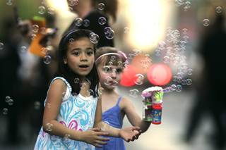 New friends Mikayla Benitez (L) and Eden Fuller play with a bubble gun Saturday during the annual Helldorado Parade.