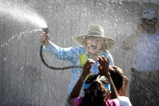 Principal Kelly Strudy sprays students with a hose during field day at Fay Herron Elementary School in North Las Vegas Thursday, May 20, 2010.
