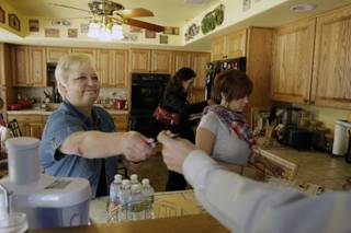 Former Assemblywoman Kathy McClain, Democratic candidate for Senate District Seven, hands out supplies to volunteers in her kitchen before canvassing neighborhoods Monday May 24, 2010. McClain faces another former assembly veteran Mark Manendo in the June 8 primary.