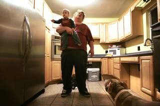Jack Rode holds his two-year-old grandson Latreovion Mendoza after putting away groceries in the kitchen of his Las Vegas home Wednesday, May 26, 2010.  The mother of Rode's children and his 28 year companion Donna Wendt died March 13, 2009 after an accident at Sunrise Hospital Medical Center. Her windpipe was torn open when they inserted a breathing tube, causing oxygen to be pumped into her body instead of her lungs. The torn windpipe was not immediately detected, allowing air to be pumped into her chest cavity for about 24 hours. Just before her death, they had finished remodeling their kitchen to be accessible for Wendt, who was wheelchair-bound, with low countertops, a raised dishwasher and oven, and pull out drawers and cabinets for easy access.