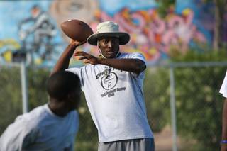 Oklahoma defensive back Quinton Carter runs reception drills while coaching his youth football team during a football camp Sunday night at Ed Fountain Park in 2010.