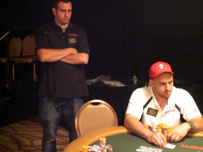 "Robert Mizrachi, left, watches on as his brother Michael ""The Grinder"" Mizrachi, right, plays a hand in the $50,000 Poker Player's Championship Monday at the Rio. The brothers will play together for a shot at $1.56 million and a gold bracelet tonight at the final table."