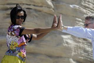 First lady Michelle Obama and Senate Majority Leader Harry Reid stretch during an exercise activity Tuesday at the Red Rock Canyon National Conservation Area. Obama, Reid Assistant Secretary of the Interior Rhea Suh kicked off the national