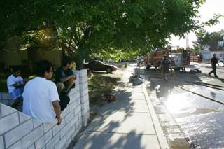 Neighbors watch the cleanup at the scene of a fire where two people were found dead on Thursday near the intersection of Decatur and Lake Mead boulevards.