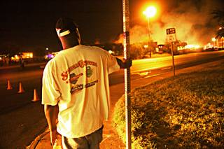 Sann Atkins, 36, of Las Vegas stands at the corner of Boulder Highway and King Street watching a four-alarm fire at a pallet yard across the street. Atkins is part owner of the Legacy Auto Shop, which is across the street from the yard that caught fire Tuesday.  Police and firefighters were not allowing anyone near the blaze, so at the time of the photo, Atkins did not know whether his shop had been damaged.