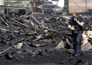 A Henderson Fire Department investigator holds a mask to his face Wednesday as he walks through rubble the day after a fire in a Henderson pallet yard near Boulder Highway and West Barrett Street.