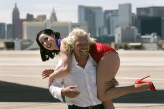 Virgin Airlines President Richard Branson carries burlesque star Dita Von Teese on his shoulders during a media event to mark the 10th anniversary of Virgin Atlantic's London to Las Vegas route Tuesday, June 15, 2010.