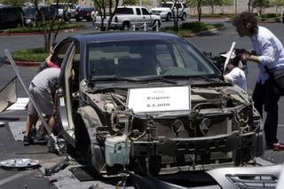 Boys look inside a stripped 2007 Toyota Camry during a