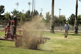 Herman Britz, a park maintenance worker, uses a Rodenator to blow up gopher holes Tuesday in Sunset Park.