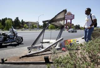 Torri Jasper looks over a bus shelter after an accident on Rancho Drive just north of Lake Mead Boulevard Monday, June 21, 2010. The driver of a northbound pickup truck ran the red light, colliding with another vehicle before hitting the shelter. The driver of the truck, a person waiting at the bus shelter and the driver of another vehicle were transported to the hospital, police said.