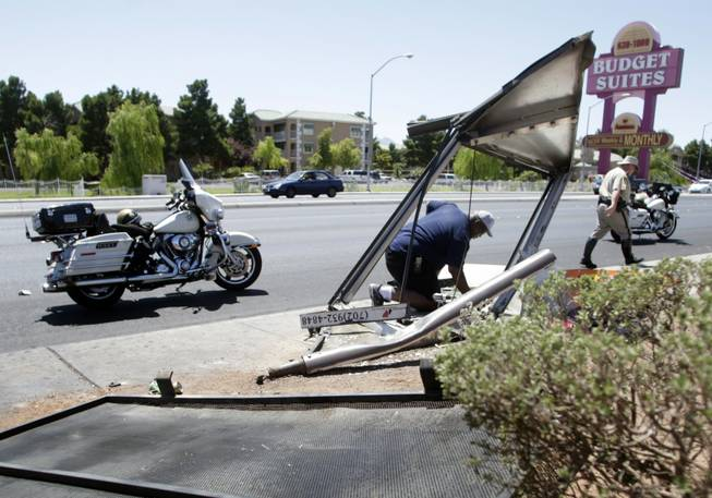 Reginald Lovett, an employee of Outdoor Promotions, disconnects electricity from a bus shelter after a pickup truck ran into the shelter on Rancho Drive just north of Lake Mead Boulevard Monday, June 21, 2010. The driver of the truck, a person waiting at the bus shelter and the driver of another vehicle were transported to the hospital, police said.