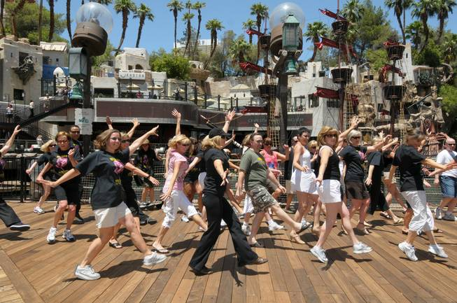 Former cast members dance in front of Treasure Island during the 70th anniversary reunion of the Ice Capades on June 22, 2010.