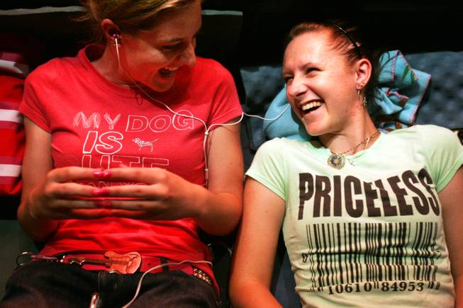Kristi DeVita, left, and her friend Katie Ritchie, both of Boulder City, share ear buds and listen to music while waiting in line for the new iPhone 4 outside the Apple store in Town Square in Las Vegas Wednesday, June 23, 2010. The store opened at 7 a.m. Thursday, June 24.