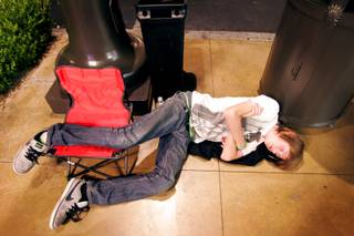 Alex Asay, 13, of Las Vegas takes a nap by a trash can while waiting in line for the new iPhone 4 just before sunrise outside the Apple store in Town Square in Las Vegas Thursday, June 24, 2010. The store opened at 7 a.m.