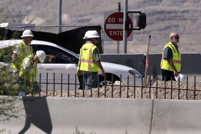 Workers wait as officials investigate a fatal construction accident on Blue Diamond Road by the I-15 northbound on-ramp Tuesday, June 29, 2010.