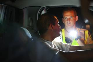 An unidentified driver complies with commands while being examined by Metro Police Officer Eric Hutchason during a vehicle stop Friday, July 2, 2010, at a DUI checkpoint on Nellis Boulevard south of East Lake Mead Boulevard.