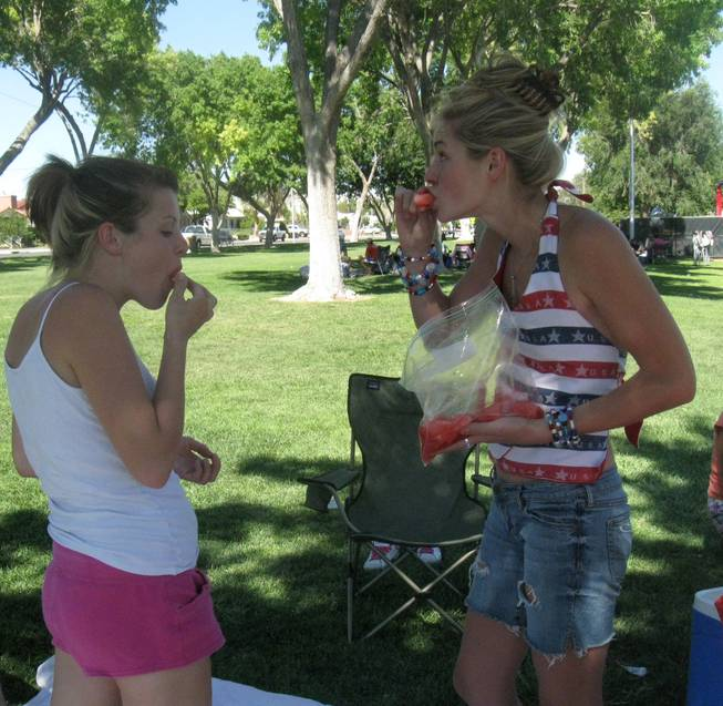 From left, Betsy Lockwood, 21, and Katelyn Conrad, 20, eat watermelon Saturday at Memorial Park during Boulder City's 62nd annual Damboree Celebration.