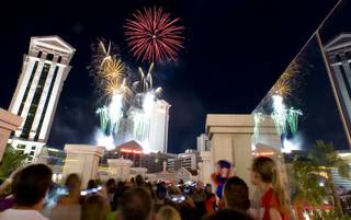 People watch fireworks over Caesars palace from a pedestrian bridge over the Las Vegas Strip on Sunday, July 4, 2010.