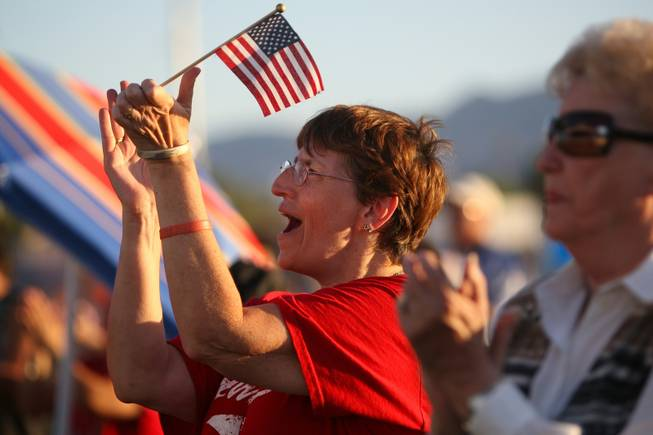 Michelle Parker applauds during the playing of patriotic songs during Henderson's Fourth of July celebration Sunday night at Basic High School.