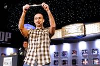 Daniel Alaei raises the gold bracelet he won for finishing first in the $10,000 Pot Limit Omaha tournament at the World Series of Poker.