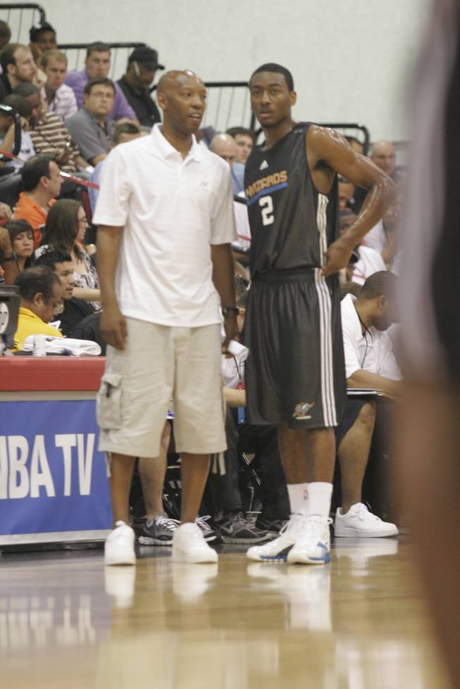 Washington guard John Wall, right, talks during a break in the action on Sunday with Wizards coach Sam Cassell. Wall, the top pick in last month's NBA draft, led the Wizards to an 84-79 victory over the Golden State Warriors in his team's Summer League opener at the Cox Pavilion with 24 points and eight assists.