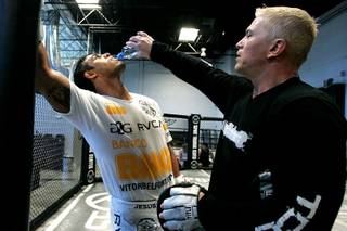 Brazilian middleweight Vitor Belfort gets a drink from trainer Shawn Tompkins after a workout at TapouT Wednesday, July 14, 2010.