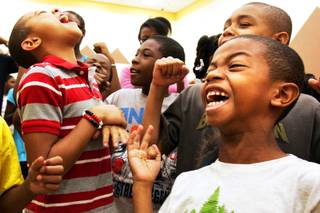 Benjamin Horsford, from left in red stripes, Gregory Oliver, in grey, and Bryson Horsford, front right, sing and dance during the morning Harambee session at Rainbow Dreams Academy in Las Vegas Thursday, July 22, 2010.