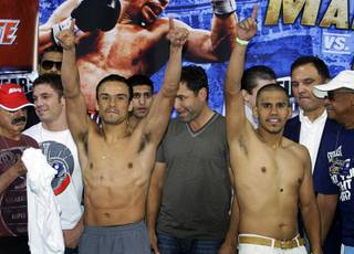 WBA/WBO lightweight champion Juan Manuel Marquez, left, of Mexico City and Juan Diaz of Houston, Texas pose during an official weigh-in at the Mandalay Bay Events Center Friday, July 30, 2010. The boxers meet for a rematch at the events center on Saturday.