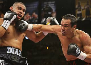 Juan Diaz, left, of Houston, Texas takes a punch from Juan Manuel Marquez of Mexico City during the WBA/WBO lightweight title fight at the Mandalay Bay Events Center in Las Vegas on July 31, 2010.