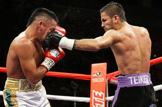 Rocky Juarez, left, of Houston, Texas, takes a punch from Jorge Linares of Venezuela during the WBA Fedelatin lightweight title fight Saturday at the Mandalay Bay Events Center.
