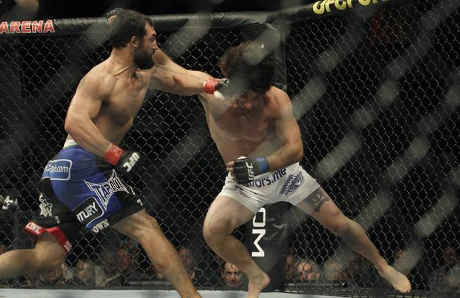 Charlie Brenneman, right, and Johny Hendricks, left, exchange punches at UFC 117 in Oakland, Calif.