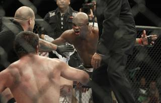 Anderson Silva, center, celebrates in front of Chael Sonnen after submitting Sonnen in the fifth round during a middleweight championship fight at UFC 117 on Saturday in Oakland, Calif. Silva retained his championship.