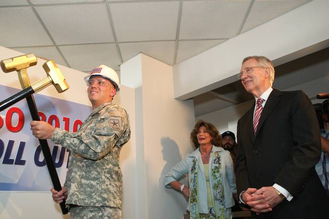 U.S. Sen. Harry Reid and U.S. Rep. Shelley Berkley (both D-Nev.) watch on as Sgt. Jason Schwartz crosses a gold sledge hammer prior to ceremoniously hitting a wall inside the new USO lounge during the groundbreaking ceremony in Terminal 1 at McCarran International Airport on Wednesday, August 18, 2010.