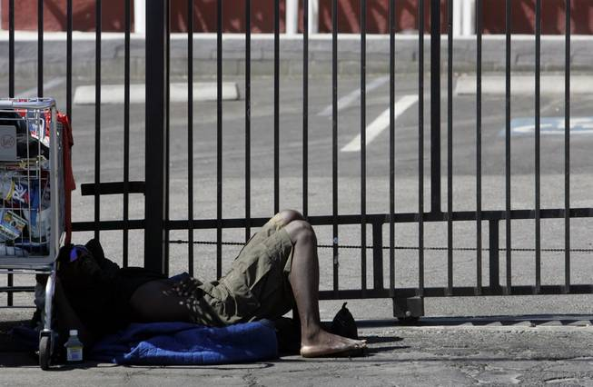 A homeless man takes a nap on Foremaster Lane last summer. Homelessness is a factor in the redevelopment of downtown Las Vegas.