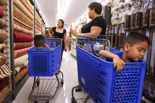 Jennifer Rodriguez, left, shops with her mother, Maria Quiralte, and 4-year-old twins Anthony and David, right, at the new Hobby Lobby in Henderson. The store, the 441st in the chain, opened Monday in a 51,000-square-foot space formerly occupied by a Von's supermarket. Even as many retailers and food establishments are struggling to outlast the recession, new franchises are entering the market or expanding their foothold.