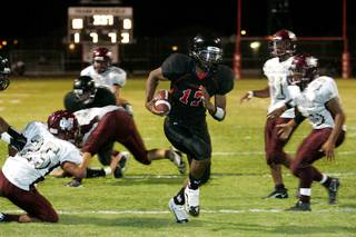 Las Vegas quarterback Hassan Henderson finds a hole for a touchdown against Cimarron-Memorial on Thursday during the first high school football game of the season. Las Vegas won the game 34-15.