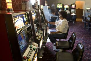Yolanda Mua'e plays slots in the Cal-Nev-Ari Casino Thursday, Sept. 2, 2010. The community, started by California pilots Nancy and Slim Kidwell in the 1960s, is up for sale  for $17 million.