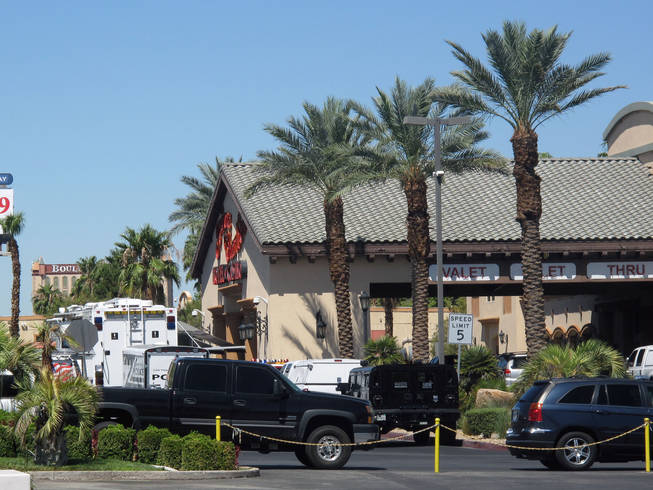 Police clean up their equipment Saturday morning after responding to a man who claimed to have a bomb at Arizona Charlie's Boulder Hotel and Casino. The bomb ended up being a hoax, police said.