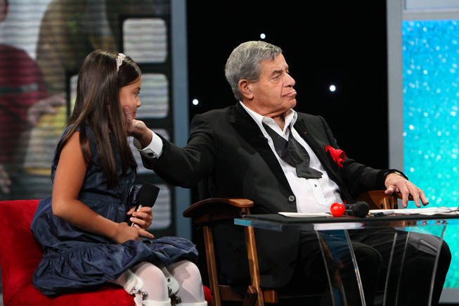 "After sharing ""I love yous,"" Jerry Lewis fondly touches Abbey Umali's face Monday afternoon during the final hour of the 45th Annual Jerry Lewis MDA Labor Day Telethon at the South Point. Umali is the 2010 MDA youth ambassador."