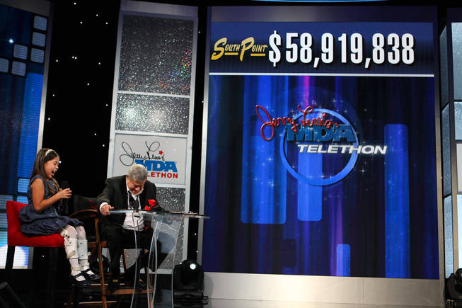 Jerry Lewis and 2010 MDA ambassador Abbey Umali celebrate the final tally of $58,919,838 as it appears on the tote board Monday afternoon during the final hour of the 45th Annual Jerry Lewis MDA Labor Day Telethon at the South Point.