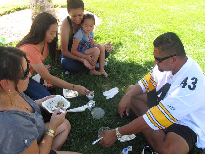 Family members (from left to right) Michelle Olivé, Kristen Uy, 16, Mariah Olivé, 15, Masina Olivé, 5, and Tau Olivé enjoy a picnic of Hawaiian food at the Prince Jonah Ho'olaule'a Pacific Islands Festival in Henderson on Sunday. The family has been coming to the festival for several years.