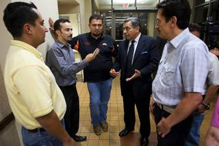Latinos, including Emmanuel Corales, center left, Marco Hernandez, center, and Fernando Romero, president of Hispanics in Politics, talk following a community meeting Tuesday at the East Las Vegas Community Center. The meeting was held to address concerns following immigration raids in July at local bus stations.