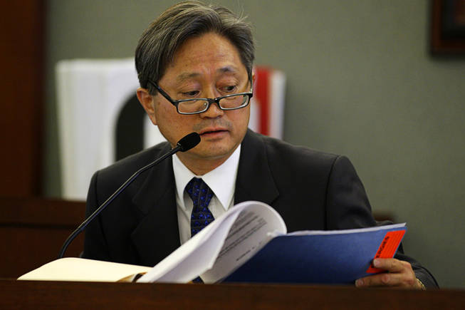 Dr. Daniel Kim, one of Erik Scott's physicians, looks through medical records during a coroner's inquest at the Regional Justice Center Wednesday, September 22, 2010.