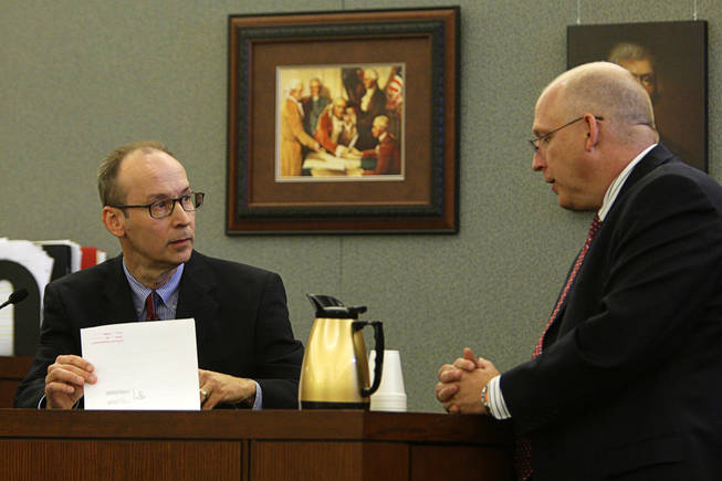 Dr. Joseph Gnoyski, left, one of Erik Scott's physicians, listens to Chief Deputy District Attorney Christopher Laurent during a coroner's inquest at the Regional Justice Center Wednesday, September 22, 2010.
