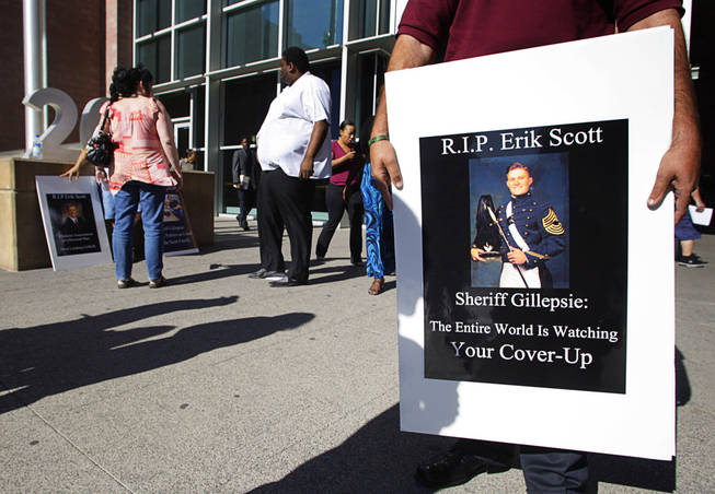 Dustin Deguevara holds a sign in front of the Regional Justice Center before a coroner's inquest into the shooting of Erik Scott Wednesday, September 22, 2010. Scott was shot and killed by Metro Police Officers at the Summerlin Costco on July 10. Deguevara said he is best friends with Erik's younger brother.