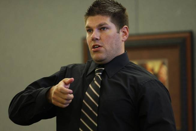 Shai Lierley, a Costco loss prevention supervisor, demonstrates how Erik Scott brought his gun on an officer as he testifies during a coroner's inquest at the Regional Justice Center Thursday, September 23, 2010.