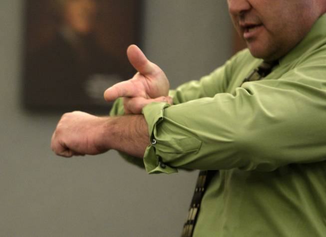 Steven Novotny demonstrates how Erik Scott pointed a gun at him and his dog as he testifies during a coroner's inquest at the Regional Justice Center Thursday, September 23, 2010. Novotny said the event occurred after his dog got loose and bit Scott.