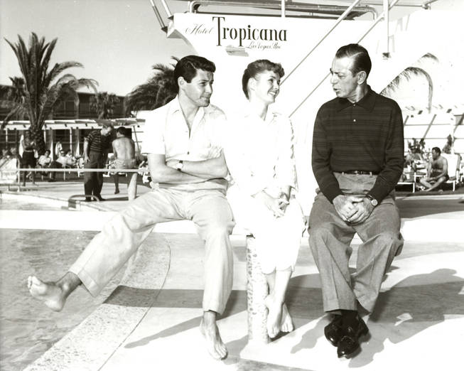 In this photo provided by Las Vegas News Bureau, Eddie Fisher and wife Debbie Reynolds chat with veteran entertainer Eddie Cantor at the Tropicana pool on April 25, 1957.