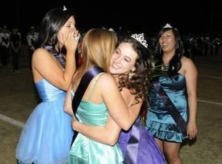 Coronado Homecoming Queen KaitlynThompson, right center, gets a big hug from Glory Finnegan as they celebrate during halftime festivities of the game between the Cougars and visiting Gators on Friday night. At left is Kiki Posner and at right is Kathy Chao.