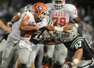 De La Salle's Dylan Wynn (67) gets pushed back by Bishop Gorman quarterback Anu Solomon (12) in the second quarter of Saturday's game in Concord, Calif.